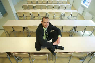 Jacek Sitting on a Table in a Classroom