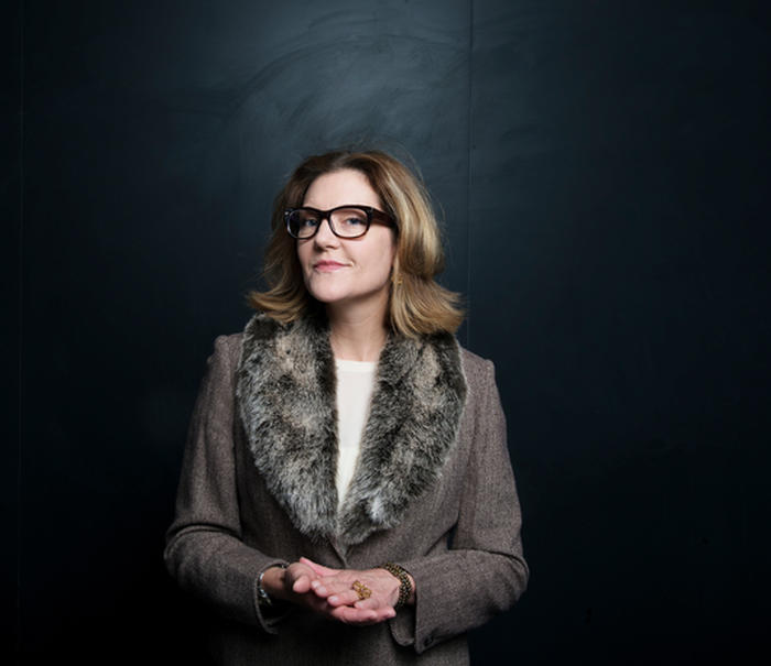 Kathleen Vohs poses in front of a black background