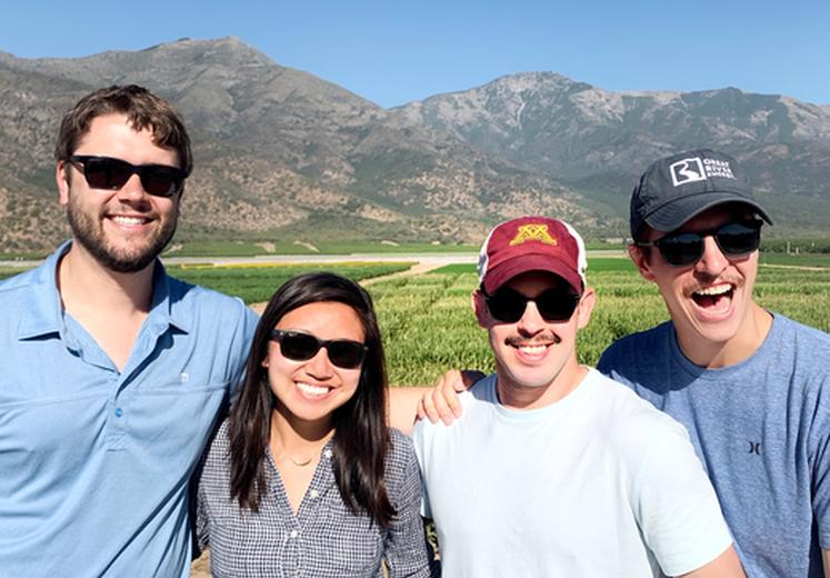 Four Carlson students stand and smile in front of the Andes mountains, against a blue sky.