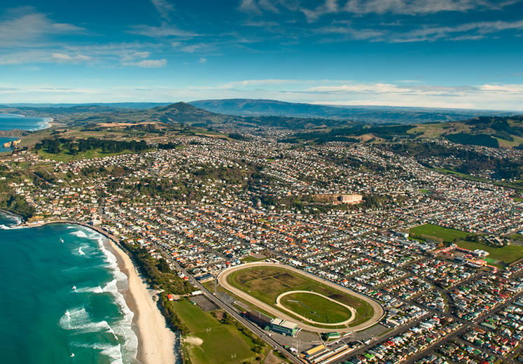 Bird's eye view of Dunedin, New Zealad, with a blue sky, mountains in the background, and crashing waves along the coast.