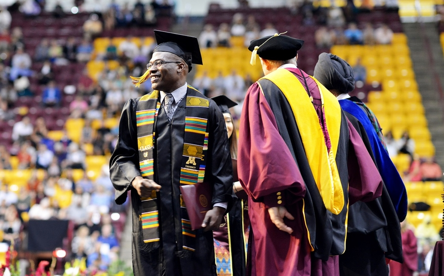 Ujay Green walks across the stage at the Carlson School's undergraduate graduation ceremony May 15.