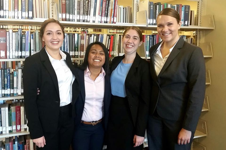A Case Study Team Posed Together and Smiling in a Library